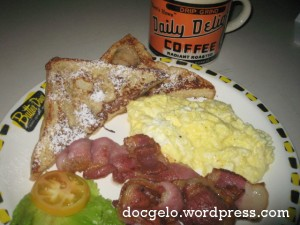 four bacon strips, 2 scrambled eggs, french toasts with maple syrup & butter & a mug of hot brewed coffee